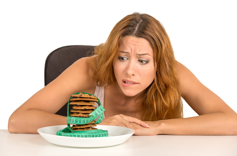 Portrait young unhappy woman craving sugar sweet cookies but worried about weight gain sitting at table isolated on white background. Human face expression emotion. Diet nutrition dilemma concept
